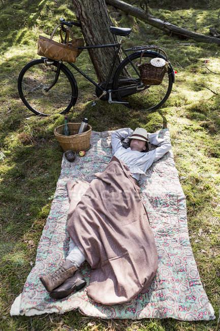 Forrageira de feminina madura descansando em cobertor na floresta — Fotografia de Stock