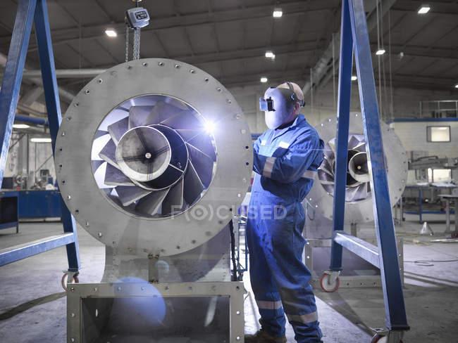 Engineer welding airduct part in engineering factory — Stock Photo