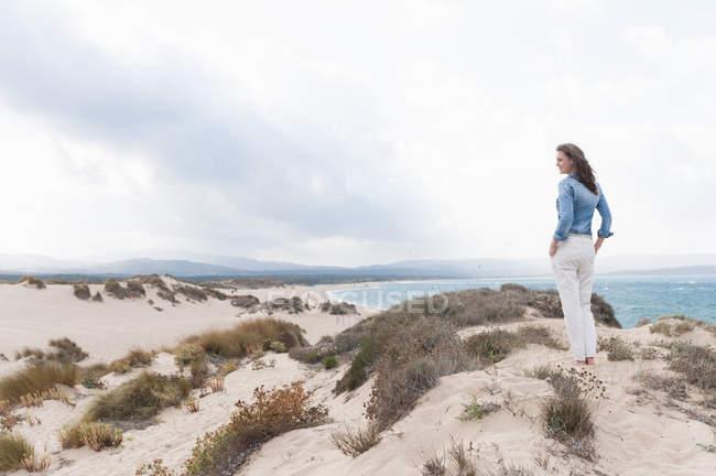 Femme adulte moyen au-dessus des dunes de sable regardant la vue, Sardaigne, Italie — Photo de stock