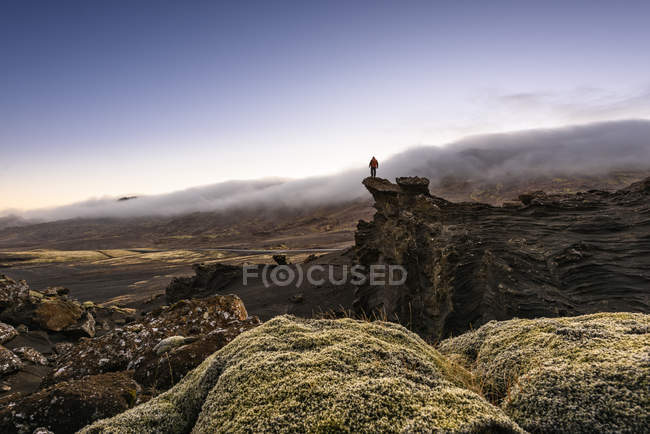 Male hiker on rock formation looking out at mist over mountain tops — Stock Photo