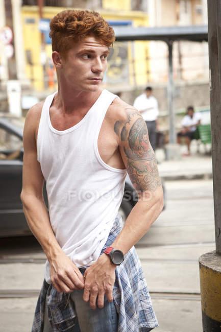 Giovane in strada, con in mano una tasca di pantaloni, distogliendo lo sguardo — Foto stock