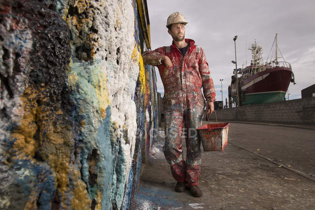 Male ship painter holding paint can leaning against paint splattered wall — Stock Photo