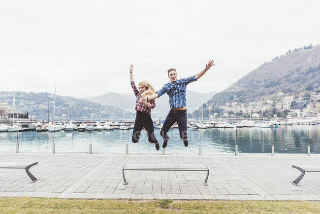 Young couple on waterfront jumping mid air, Lake Como, Italy — Stock Photo