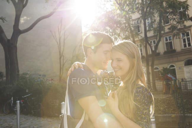Молодая пара обнимается на пригородной улице — стоковое фото