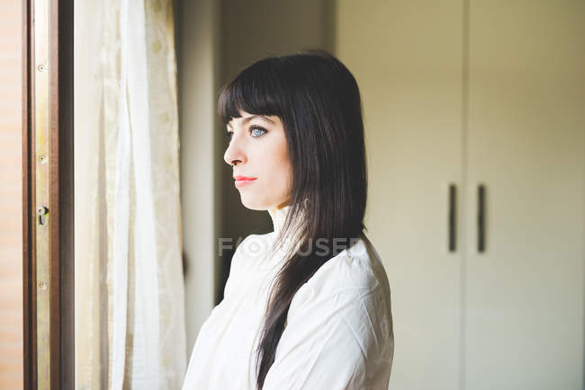 Young woman looking out of window — Stock Photo