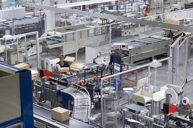 Работники мужского и женского пола, работающие на бумажной фабрике — стоковое фото