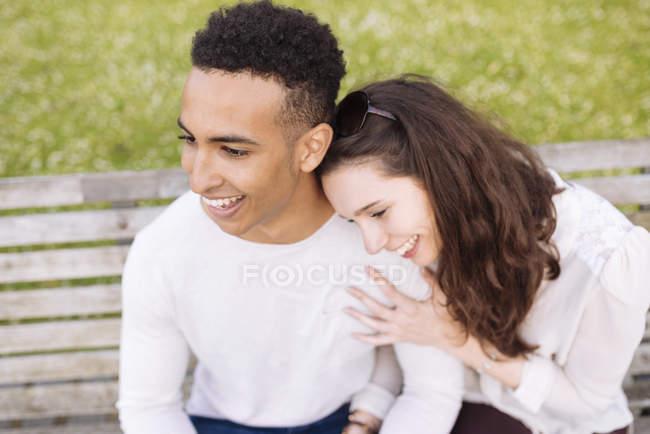 Вид на улыбающуюся молодую пару, сидящую на скамейке в парке — стоковое фото