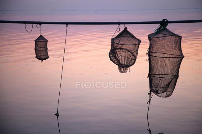 Silhueta de redes de pesca sobre água parada — Fotografia de Stock