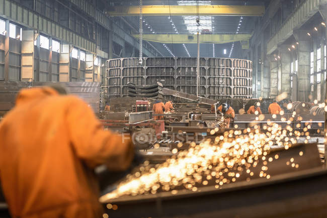 Worker grinding metal construction in marine fabrication factory — Stock Photo