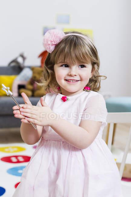 Chica en vestido rosa sosteniendo varita mágica en casa - foto de stock