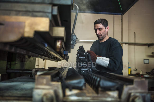 Man working in manufacturing plant on rubber production line — Stock Photo