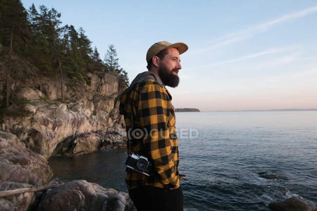 Взрослый мужчина, стоящий у озера и смотрящий на него — стоковое фото