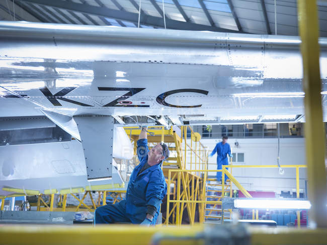 Engineer working on aircraft wing in aircraft maintenance factory — Stock Photo
