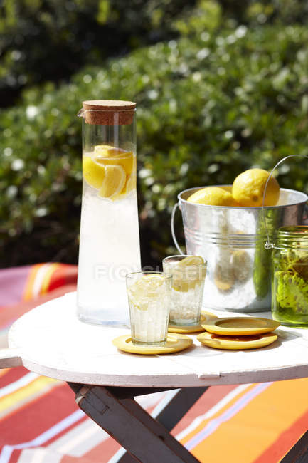 Limoncello soda in glass carafe and ice bucket of lemons on table — Stock Photo