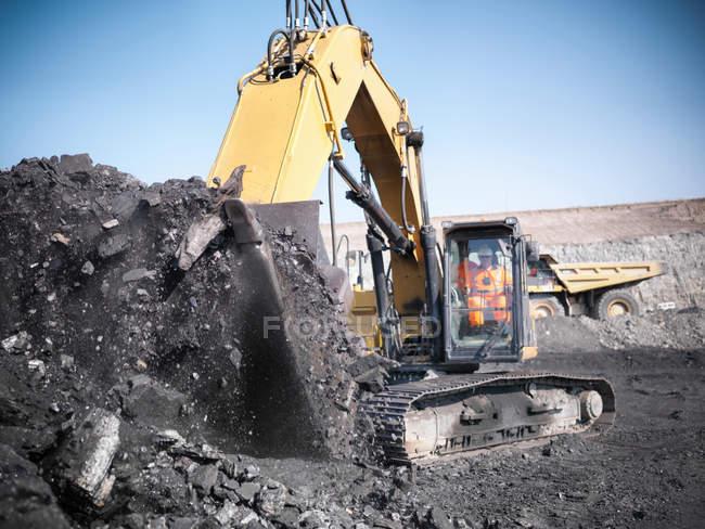 Mineur utilisant une excavatrice pour soulever le charbon d'une mine de charbon à ciel ouvert — Photo de stock