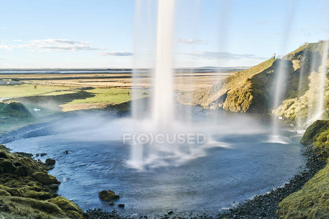 Scenic view of Behind flowing waterfall Seljalandsfoss, Iceland — Stock Photo