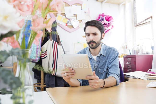 Young male designer reading digital tablet in printing press studio — Stock Photo