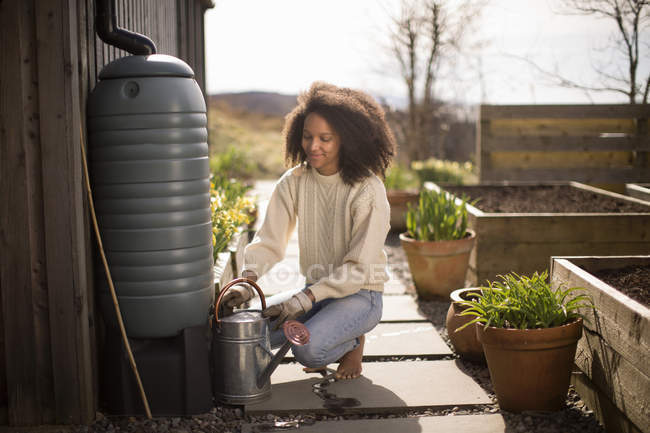 Mid adult woman filling watering can from water butt — Stock Photo