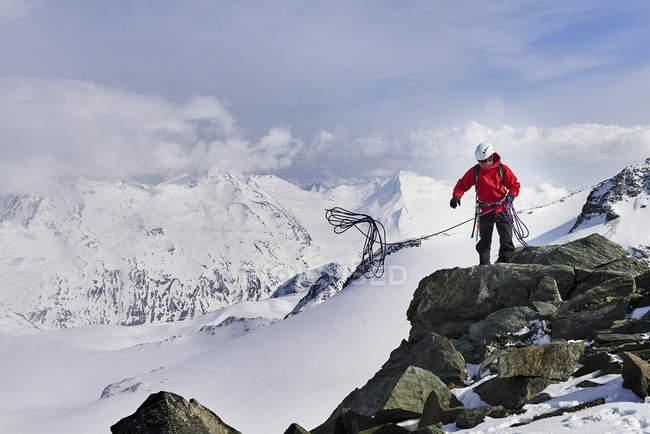 Людина на вершині сніг покриті гора кидали скелелазіння мотузку, Саас, Швейцарія — стокове фото