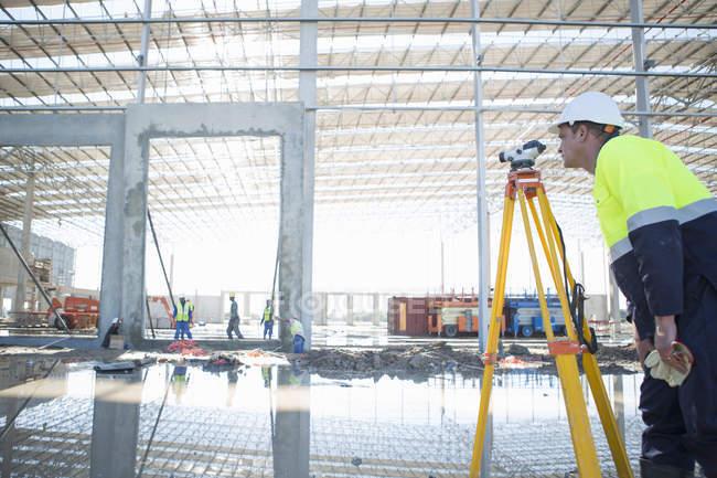 Surveyor using tripod and level on construction site — Stock Photo