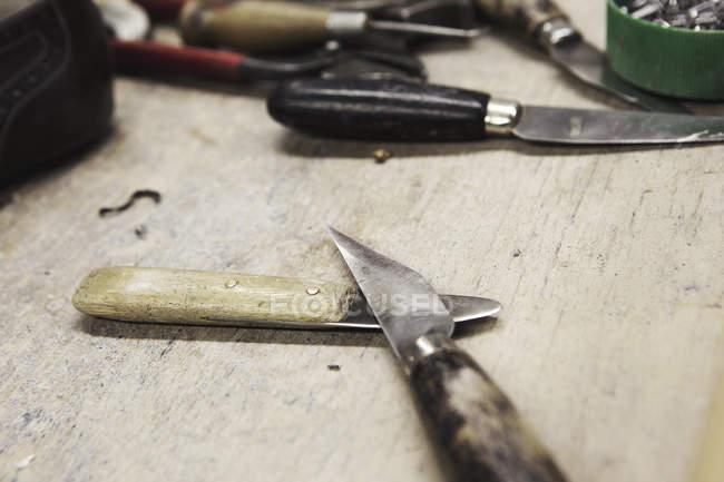 Крупним планом Ножі на лавці в майстерні виробники взуття — стокове фото