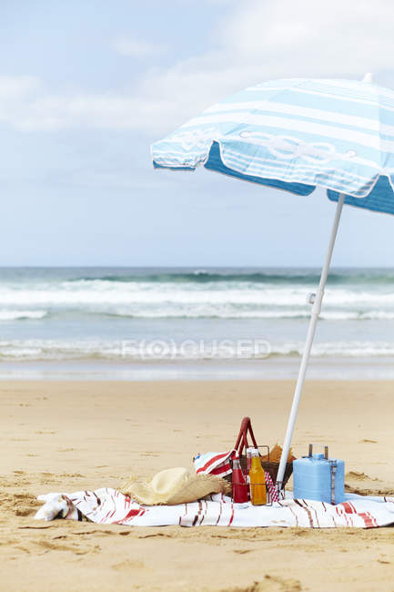 Sunhat, cool box and picnic basket on beach towel underneath parasol on beach — Stock Photo