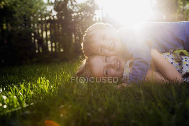 Брат и сестра лежат на траве и обнимаются с подсветкой. — стоковое фото