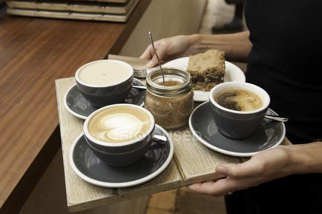 Обрезанное изображение баристы, подающей кофе — стоковое фото
