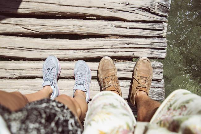 Perspectiva personal de pies de las parejas en el puente de madera, Parque Nacional de Plitvice, Croacia - foto de stock