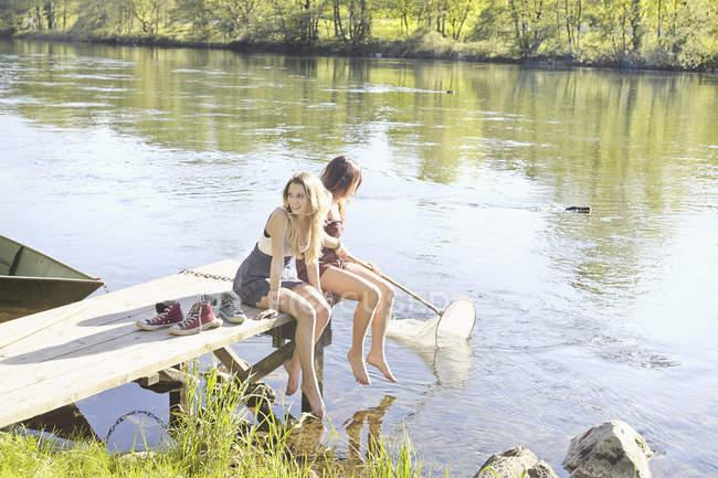 Молоді жінки сидять на дерев'яній пристані водою — стокове фото