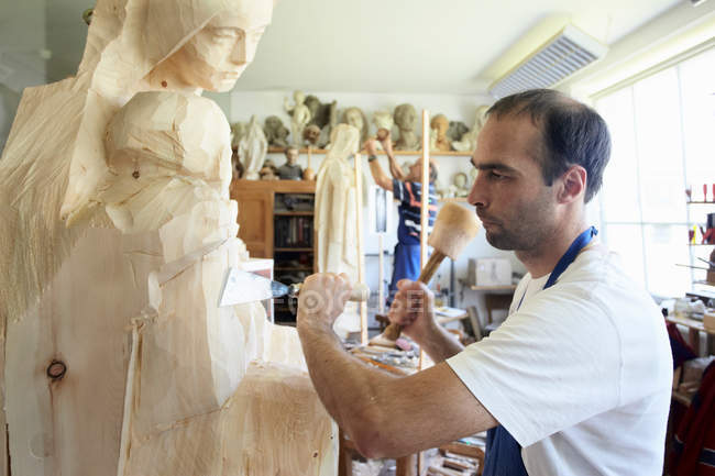 Sculptor chiseling figure from wood — Stock Photo
