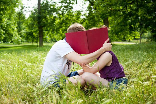 Teenager versteckt sich hinter Buch im Park — Stockfoto