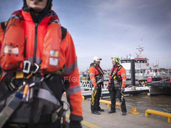 Ingénieurs de parcs éoliens offshore à quai avec des bateaux en arrière-plan — Photo de stock
