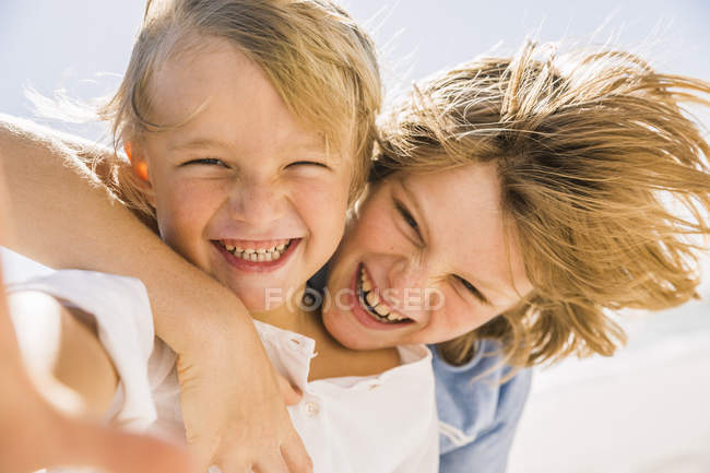 Brothers looking at camera squinting, smiling — Stock Photo