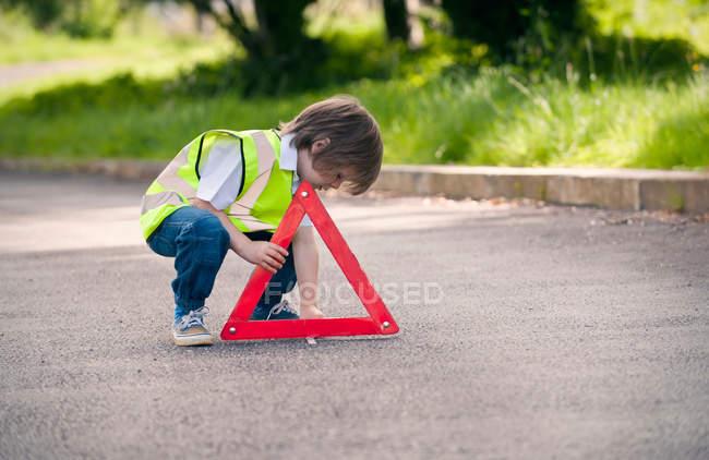 Мальчик играет в дорожного работника на сельской дороге — стоковое фото