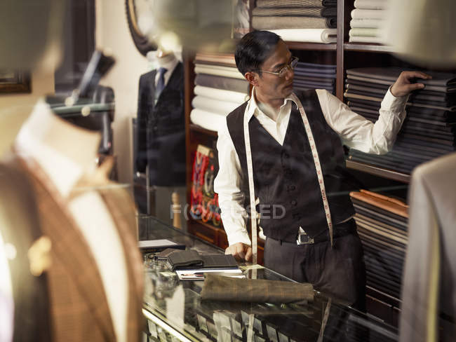 Alfaiate, escolhendo o tecido na loja tradicional alfaiates — Fotografia de Stock