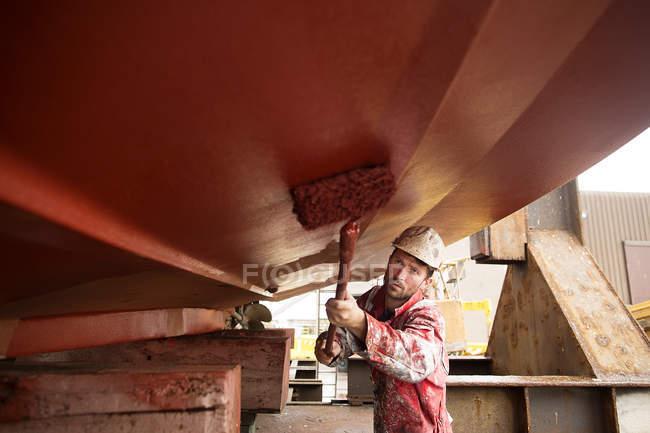 Художник-роллер под корпусом корабля на верфи корабельных художников — стоковое фото