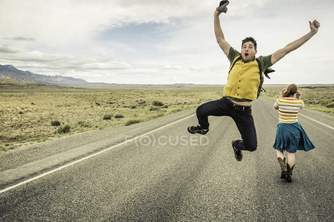 Retro style young man jumping mid air on road, Cody, Wyoming, USA — Stock Photo