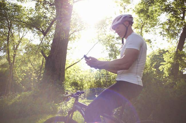 Велосипедист с помощью смартфона в лесу в подсветке — стоковое фото