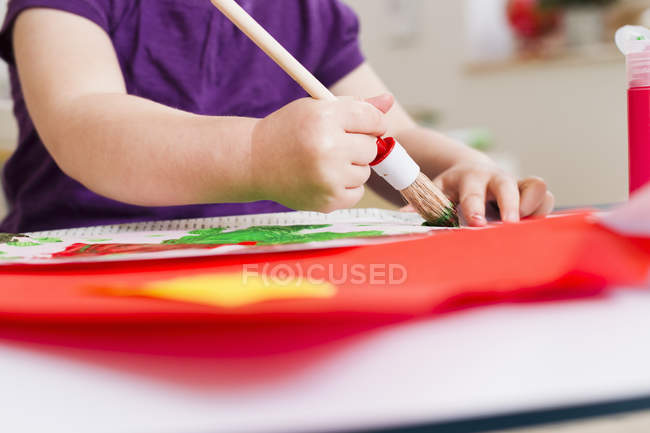 Cropped image of girl painting on paper at home — Stock Photo