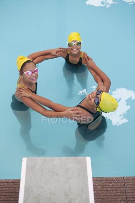 Portrait of three schoolgirl swimmers making circle — Stock Photo