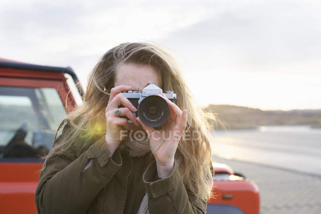 Mid adult woman photographing with SLR in coastal parking lot — Stock Photo