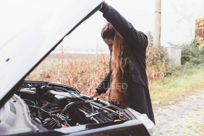 Donna guardando il motore della macchina sul ciglio della strada — Foto stock