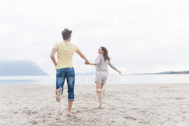 Couple running on beach together — Stock Photo