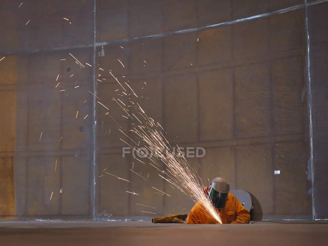 Worker grinding in marine fabrication factory — Stock Photo