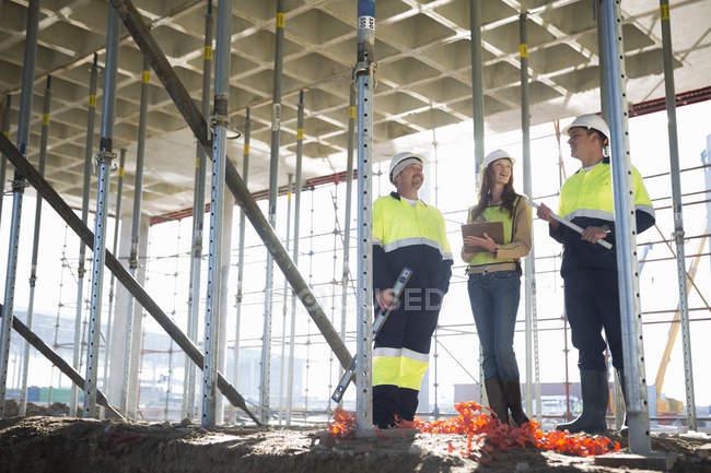 Руководитель сайта и архитекторы общаются на строительной площадке — стоковое фото