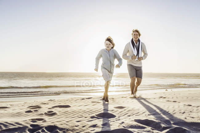 Father and son walking on beach — Stock Photo