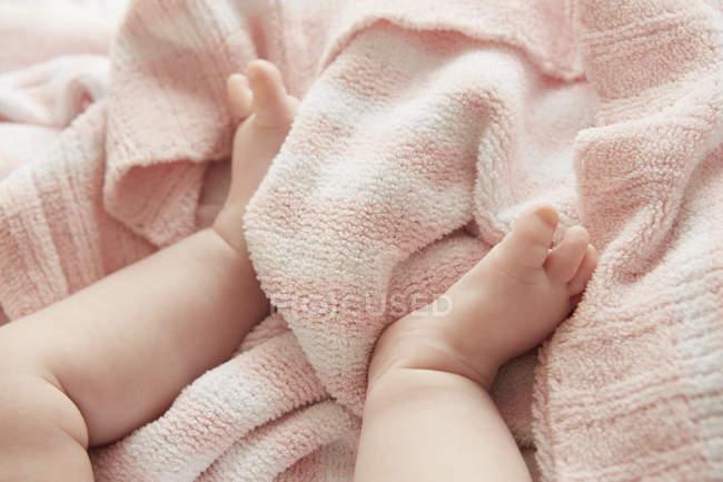 Abgeschnittenes Bild von Babybeinen auf weicher rosa Decke — Stockfoto