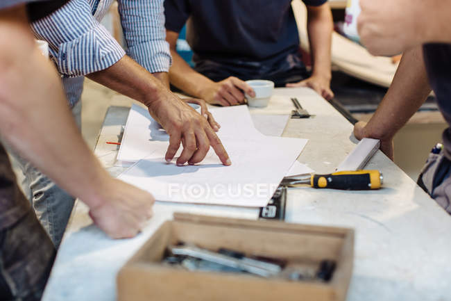 Hands of male carpenters pointing at blueprint in workshop — Stock Photo