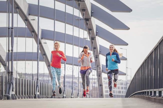 Tre corridori donne che corrono sul ponte pedonale della città — Foto stock